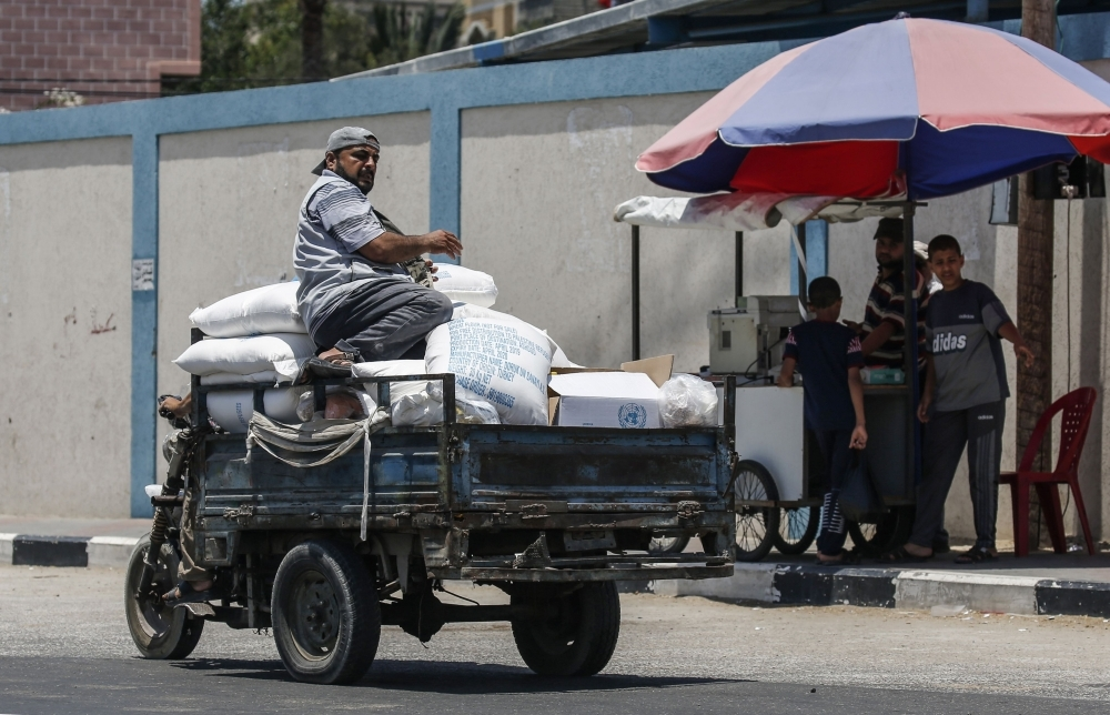 A Palestinian rides on a pickup carrying sacks of food aid provided by the United Nations Relief and Works Agency for Palestine refugees (UNRWA) in the town of Rafah, in the southern Gaza Strip, on Tuesday. — AFP
