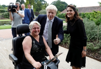 Boris Johnson, a leadership candidate for Britain's Conservative Party, poses with visitors during a walkabout at Wisley Garden Centre in Surrey, Britain, on Tuesday. — Reuters