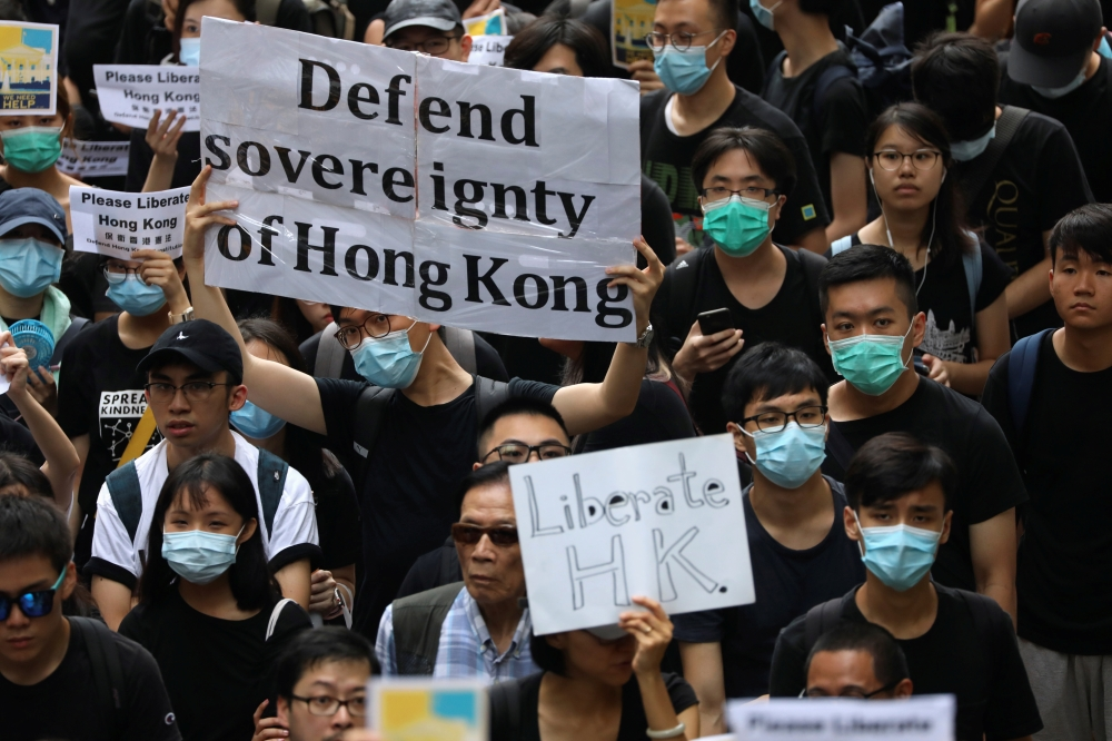 Hong Kong activists march to major international consulates in an attempt to rally foreign governments' support for their fight against a controversial extradition bill, in Hong Kong, Wednesday. -Courtesy photo
