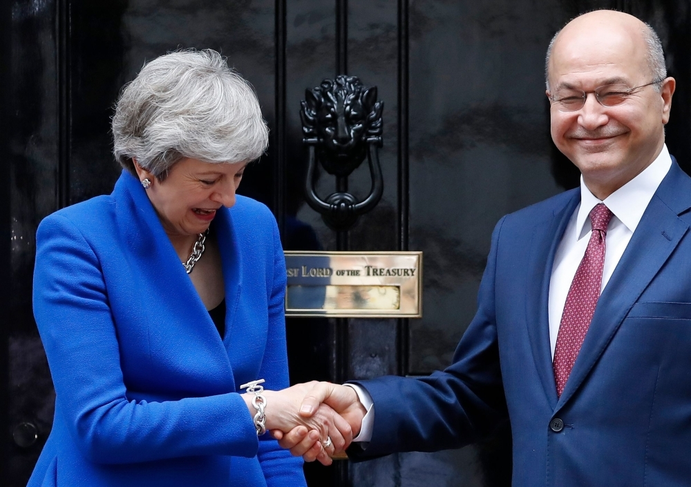 Britain's Prime Minister Theresa May, left, greets Iraq's President Barham Salih outside of 10 Downing Street in central London on Tuesday. — AFP