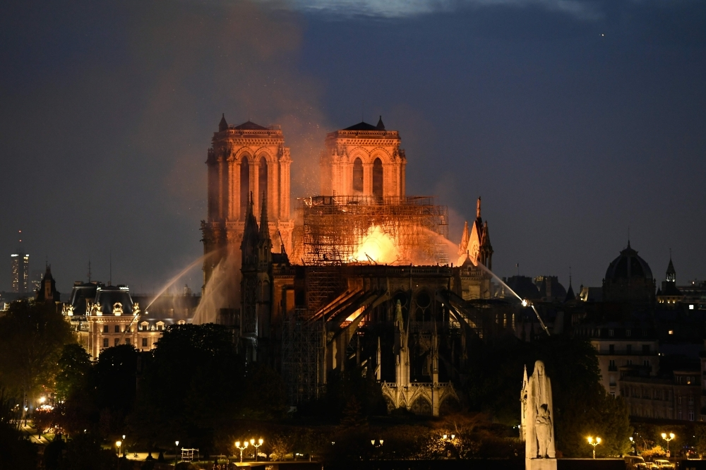 Firefighters douse flames rising from the roof at Notre-Dame Cathedral in Paris, France, in this April 15, 2019 file photo. — AFP