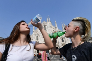 Women drink water in front of the Duomo in central Milan, Italy, during a heat wave on Wednesday. — AFP