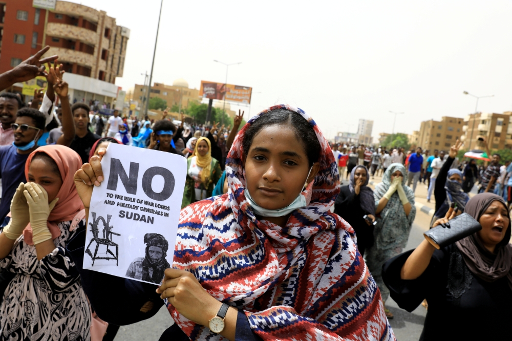 A Sudanese woman holds a placard during a demonstration demanding the ruling military hand over to civilians in Khartoum, Sudan, in this June 30, 2019 file photo. — Reuters