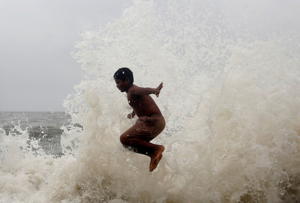 A boy plays as huge waves hit a seafront during high tide in Mumbai, India, on Thursday. — Reuters