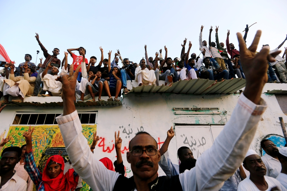 Sudanese men chant slogans as they celebrate, after Sudan's ruling military council and a coalition of opposition and protest groups reached an agreement to share power during a transition period leading to elections. — Reuters
