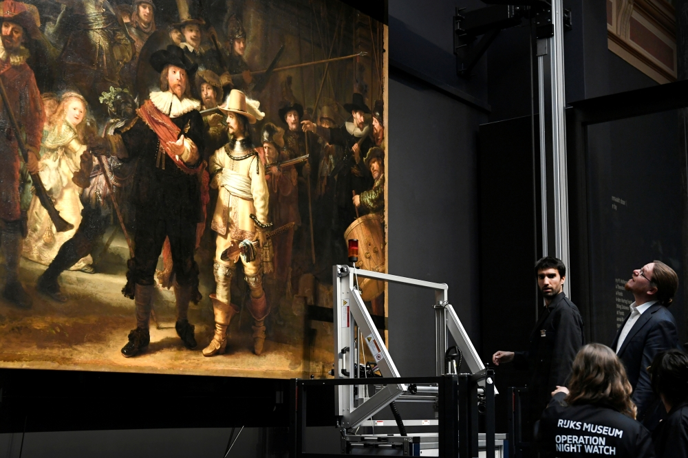 Restorers prepare Rembrandt's famous painting the 'Night Watch', protected by a glass barrier and video surveillance, as it undergoes public restoration after a first phase of study, in Rijksmuseum in Amsterdam, Netherlands Monday. — Reuters