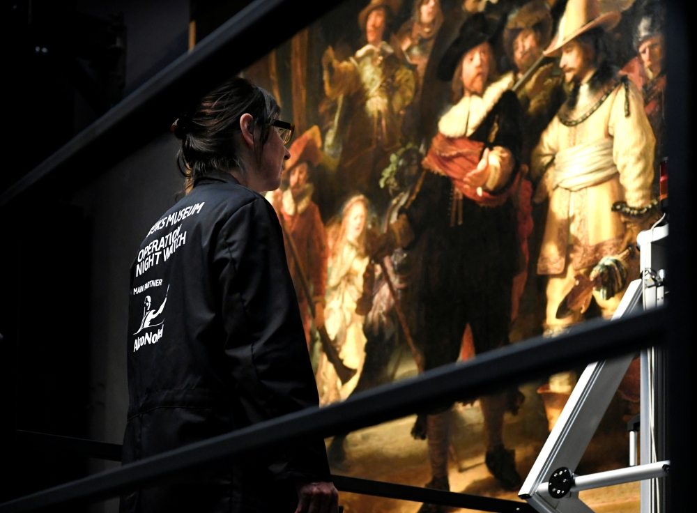 A restorer prepares Rembrandt's famous painting the 'Night Watch', protected by a glass barrier and video surveillance, as it undergoes public restoration after a first phase of study, in Rijksmuseum in Amsterdam, Netherlands Monday. — Reuters