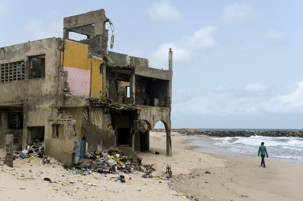 A man walks past an abandoned house destroyed by tidal erosion at Alpha Beach, a strip of the Lagos Coastline on April 29, 2019. -AFP