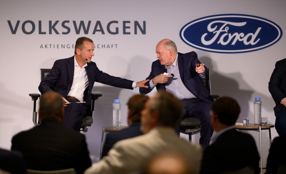 Jim Hackett (R), president and chief executive officer, Ford Motor Company, and Herbert Diess, chief executive officer, Volkswagen Group, attend a press conference Friday in New York City. — AFP