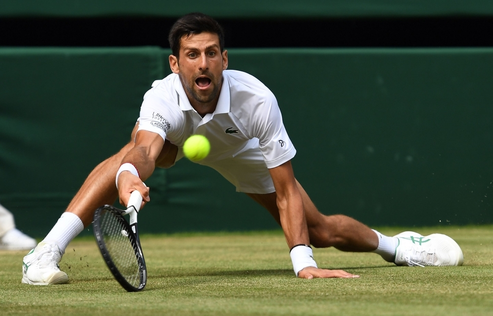 Serbia's Novak Djokovic returns against Spain's Roberto Bautista Agut during their men's singles semi-final match on day 11 of the 2019 Wimbledon Championships at The All England Lawn Tennis Club in Wimbledon, southwest London, on Friday. — AFP