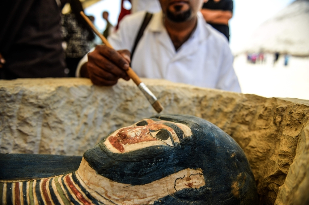A man brushes off dust from a sarcophagus, part of a new discovery carried out almost 300 meters south of King Amenemhat II's pyramid at Dahshur necropolis, exposed near the Bent Pyramid, about 40km (25 miles) south of the Egyptian capital Cairo, during an inaugural ceremony of the pyramid and its satellites, on Saturday. — AFP