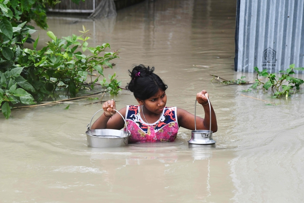 An Indian girl carries drinking water as she wades through flood waters at Pabhokathi village in Morigaon district of India's Assam state on Monday. — AFP