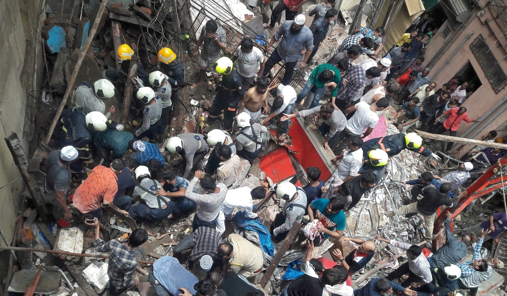 Rescue workers and residents search for survivors at the site of a collapsed building in Mumbai, on Tuesday. -Reuters photo
