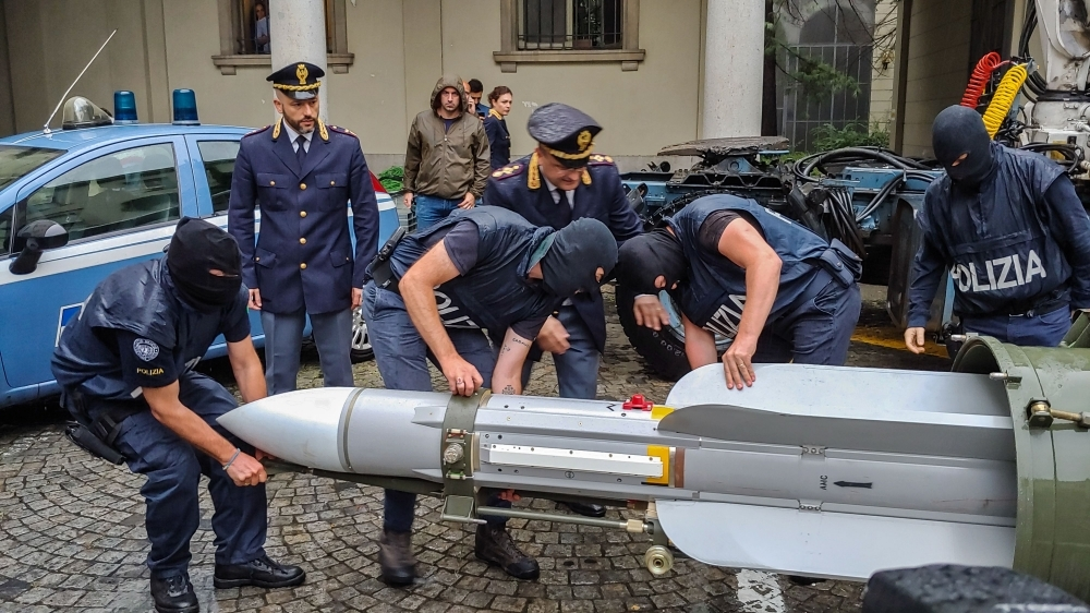 This handout picture released by the Italian police (Polizia di Stato) of Turin, on Monday, shows Italian policemen carry an air-to-air missile, as part of a big cache of guns and ammunition that was seized by the Turin special police force, called Digos, led the operations, assisted by police in Milan, Varese, Forli and Novara. — AFP
