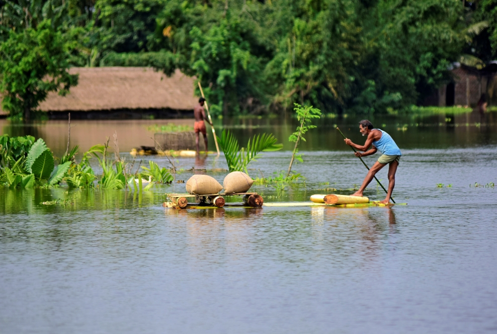 A man uses a makeshift raft to move his paddy to a safer place in a flooded area in Morigaon district in the northeastern state of Assam, India, on Tuesday. — Reuters