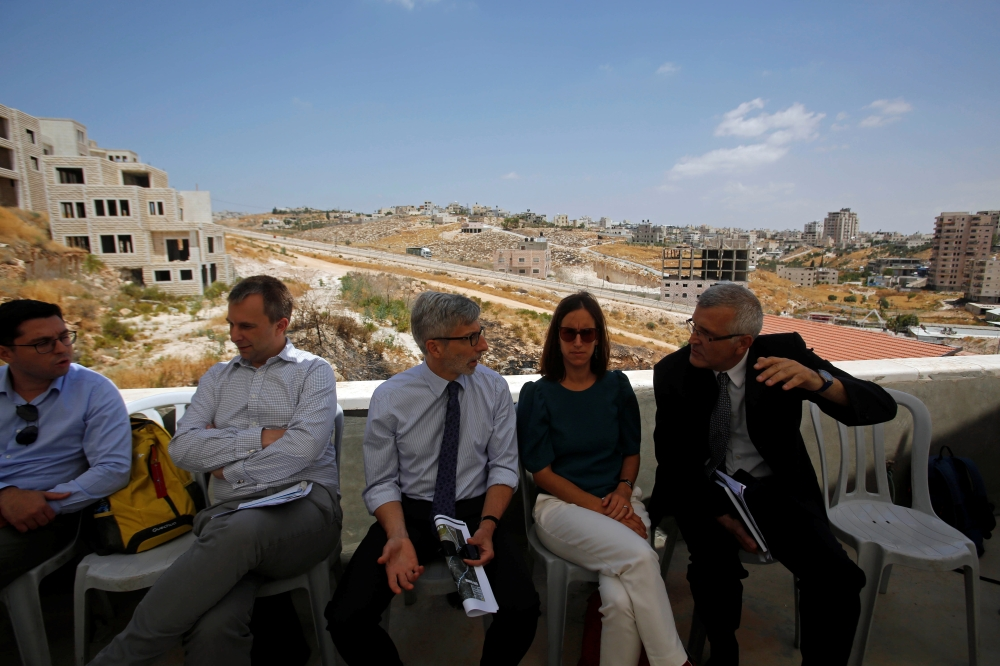 Pierre Cochard, the Consul General of France in Jerusalem, and other foreign diplomats visit Dar Salah village in the Israeli-occupied West Bank as Sur Baher, a village in the suburbs of Arab east Jerusalem, is seen in the background, on Tuesday. — Reuters