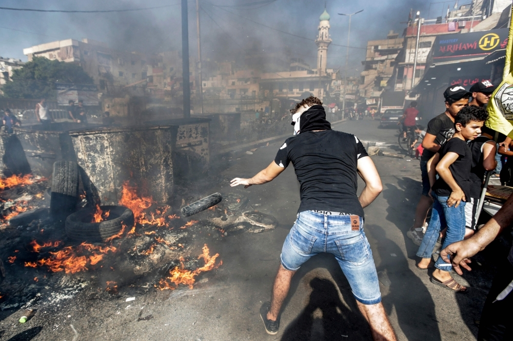 A masked man throws a tire into a fire as protesters block the main road outside the Palestinian refugee camp of Burj Al-Barajneh, south of the Lebanese capital Beirut, on Tuesday, during a protest against a decision by the Lebanese government to impose restrictions on the Palestinians' work opportunities. — AFP
