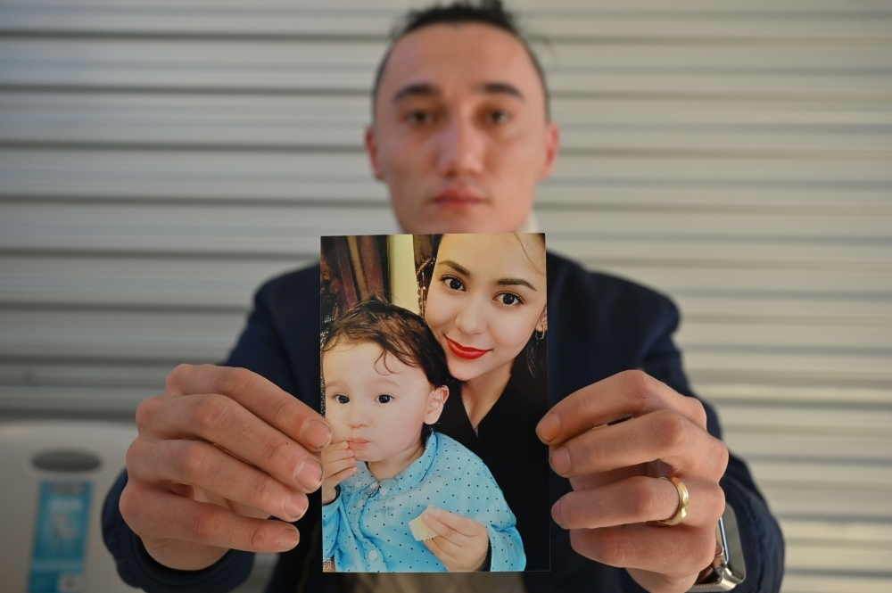 Sadam Abdusalam holds up a photo of his Uighur wife Nadila Wumaier and their baby son Lutifeier at a restaurant in Sydney's western suburbs on Wednesday. -AFP photo