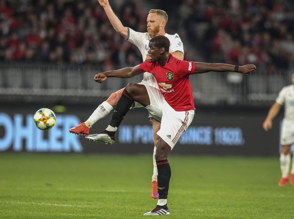 Manchester United's Paul Pogba (front) fights for the ball with Leeds United's Adam Forshaw (R) during their pre-season friendly football match at Optus Stadium in Perth, Wednesday. — AFP