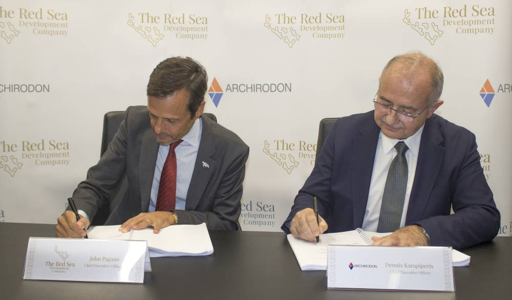 John Pagano, CEO of The Red Sea Development Company (left), and Dennis Karapiperis, CEO of Archirodon, sign the contract
