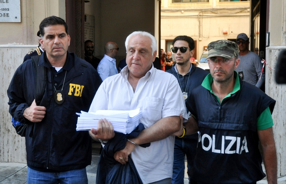 US Federal Bureau of Investigation officer, left, and Italian police officer, right, escort Tommaso Inzerillo after he was arrested in Palermo during an police/FBI operation called 'New Connection' in Palermo on Wednesday. — AFP