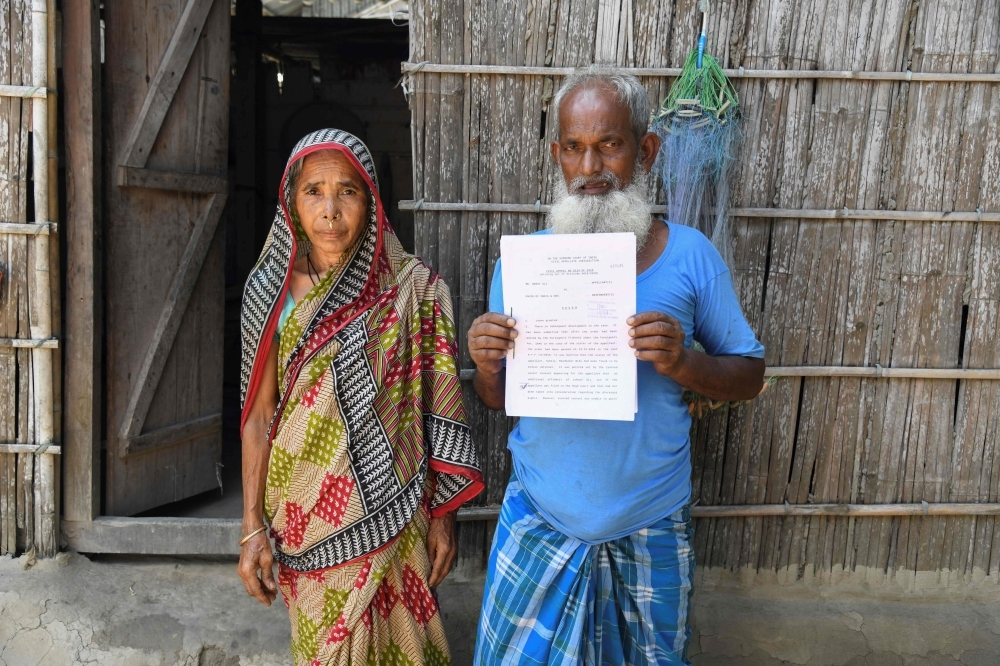 Mohammed Rehat Ali (R), 71, one of many to fall foul of a citizenship process in the north-eastern Indian state of Assam, holds a Supreme Court of India's order declaring him an Indian citizen as he stands with his wife Joiful Begum at his home at Khopnikuchi village in Assam's Kamrup district in this July 1, 2019 file photo. — AFP