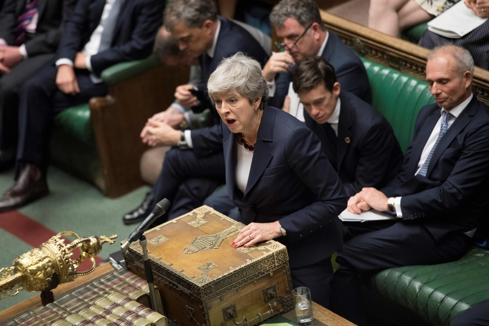Britain's Prime Minister Theresa May, center, speaks during the weekly Prime Minister's Questions (PMQs) question and answer session in the House of Commons in London on Wednesday. — AFP