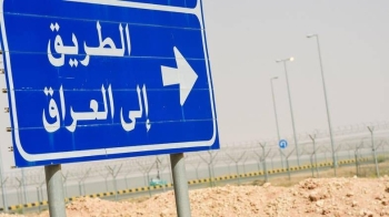 "A road sign reading in Arabic ""Road to Iraq"" near the fence separating Saudi Arabia and Iraq near Arar city. — Archives"