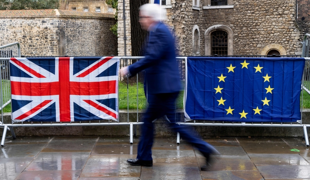 A pedestrian walks past the Union, left, and EU flags of anti-Brexit activists near the Houses of Parliament in London in this March 18, 2019 file photo. — AFP