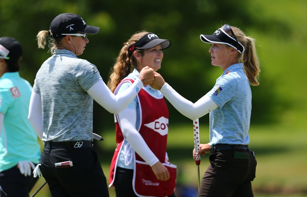 (L-R) Alena Sharp of Canada celebrates with Brooke Henderson of Canada on the ninth hole after their first round of the Dow Great Lakes Bay Invitational at Midland Country Club on Wednesdayin Midland, Michigan.  — AFP