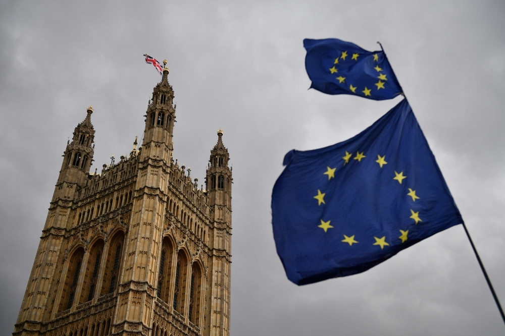 The Union flag flies atop the Houses of Parliament as EU flags held by demonstrators flutter in central London in this April 4, 2019 file photo. — AFP