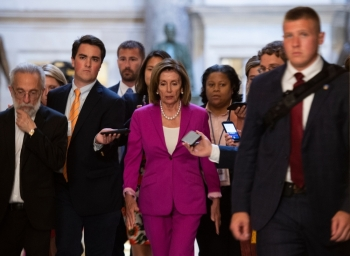 US speaker of the House, Nancy Pelosi, center, walks with reporters, before the Democrat controlled House of Representatives passed a resolution condemning US President Donald Trump for his
