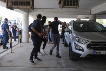Twelve Israeli tourists, suspected of raping a 19-year-old British girl in Ayia Napa, arrive to the court premises with their faces covered in the eastern Cypriot resort of Paralimni on Thursday. — AFP