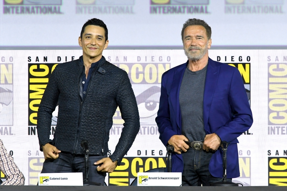 Gabriel Luna and Arnold Schwarzenegger speak at the