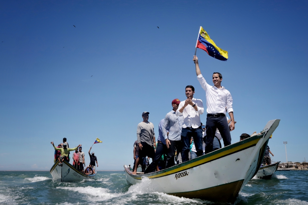 Venezuelan opposition leader Juan Guaido waves a national flag as he arrives in a boat for a meeting with supporters near Porlamar, Isla de Margarita, Venezuela, on Thursday. — Reuters
