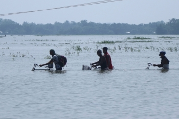 Villagers cross a submerged road with their bicycles in the flood affected area of Boko, in Kamrup district of Assam, India, on Thursday. — AFP