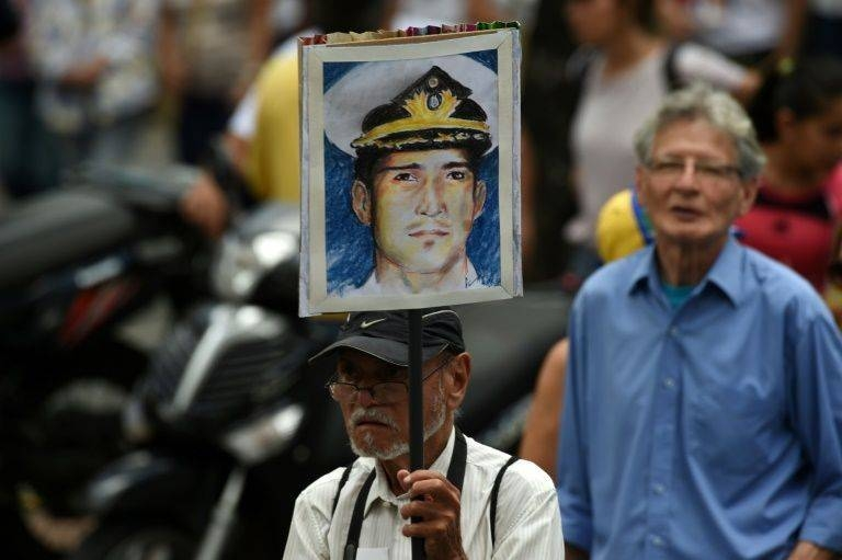 A man in Caracas holds up a portrait of Venezuelan retired naval officer Rafael Acosta, who was allegedly tortured before his death. –AFP photo