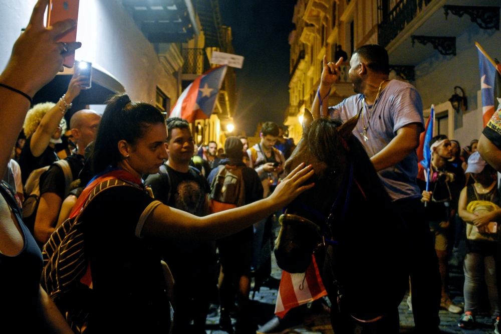 Demonstrators join the march on horses, what is called on the island a