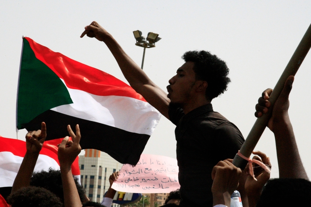 A Sudanese protester chants slogans as others wave national flags in the capital Khartoum's Green Square on July 18, as they honor comrades killed in the months-long protest movement that has rocked the country. -AFP photo