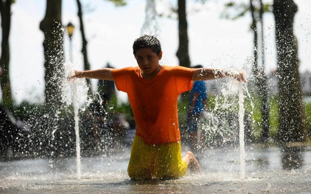 Children cool down as they play in a public fountain during summer heat on Friday in New York City. -AFP photo
