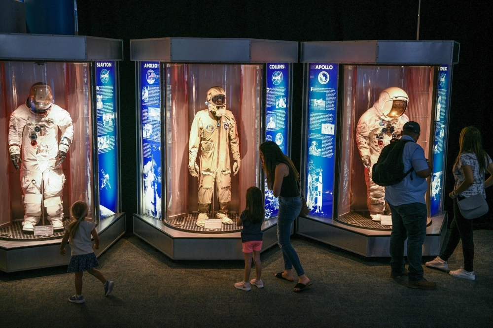 Attendees look at space suits during the Apollo 11, 50th Live celebration at Space Center Houston on Friday, in Houston, Texas. — AFP