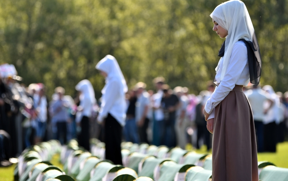 Bosnian Muslims, survivors of massacre in Western-Bosnian town of Prijedor in 1992, pray near body caskets of their relatives, as they are prepared for burial in Northern-Bosnian town of Prijedor, on Saturday. Remains of 86 newly identified bodies will be put to final rest on several local cemeteries. — AFP