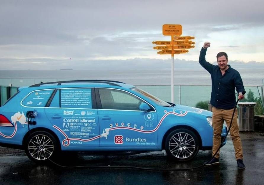 Dutchman Wiebe Wakker holds a charging cable as he poses with his electric vehicle, the Blue Bandit, after traveling 34 countries to reach Bluff, New Zealand's most southern tip, in this handout photo released Friday. — Reuters