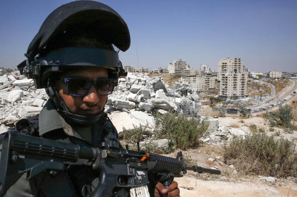 A member of the Israeli border police stands guard in front of buildings demolished by Israel in the West Bank village of Dar Salah in the area of Sur Bahir east Jerusalem, on JMonday. — AFP