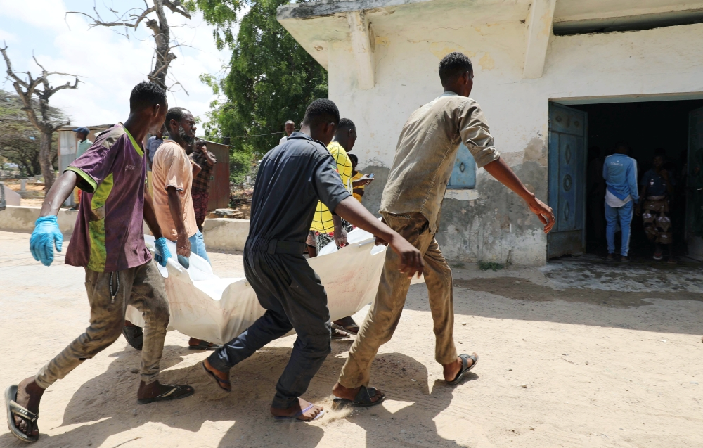 Relatives carry the dead body of a civilian killed in an explosion outside a hotel near the international airport in Mogadishu, Somalia, on Monday. — Reuters
