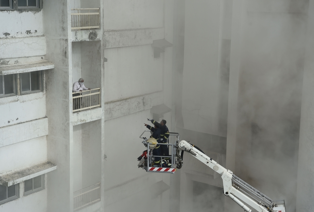 Firefighters rescue a man using a crane as he is trapped after a fire broke out in a building in Mumbai on Monday. — AFP