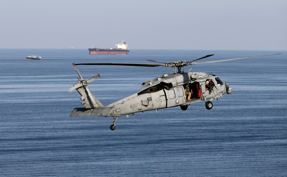 An MH-60S helicopter hovers in the air with an oil tanker in the background as the USS John C. Stennis makes its way to the Gulf through the Strait of Hormuz in this Dec. 21, 2018 file photo. — Reuters