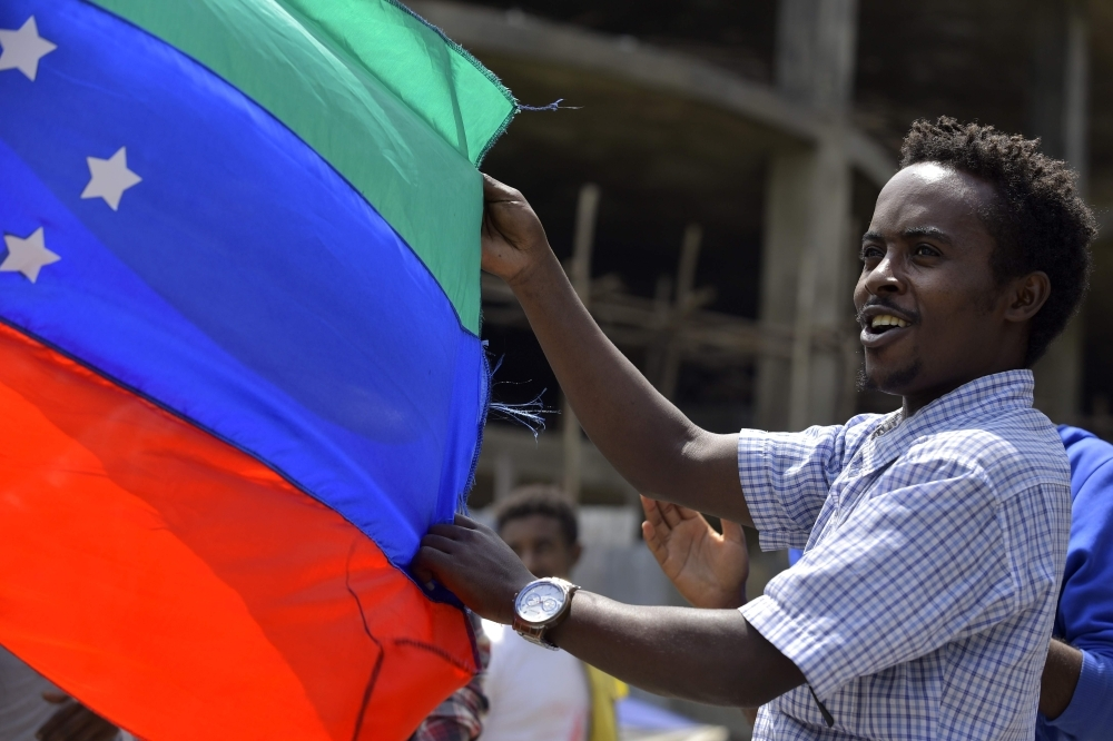 A young man holds the unofficial green, blue and red flag of the advocated region for the Sidama ethnic group in Hawassa city on July 15. -AFP photo