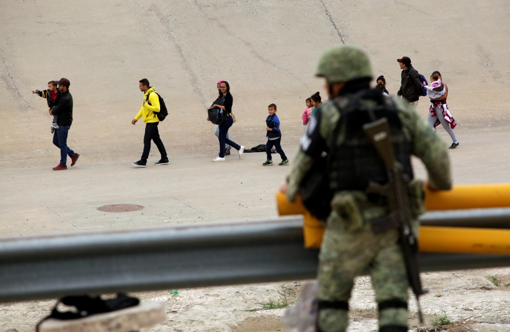 A member of the Mexican National Guard observes a group of migrants that crossed illegally into El Paso, Texas, U.S., as seen from Ciudad Juarez, Mexico on Monday. -Reuters photo