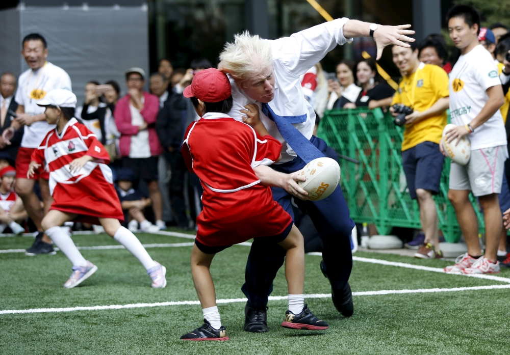 London's Mayor Boris Johnson (front R) collides with 10-year-old Toki Sekiguchi during a game of Street Rugby with a group of Tokyo children, outside the Tokyo Square Gardens building in this Oct. 15, 2015, file photo. The game was held with the attendance of school children, Nihonbashi, Yaesu and Kyobashi Community Associations and the Street Rugby Alliance to mark Japan hosting the Rugby World Cup in 2019.  — Reuters